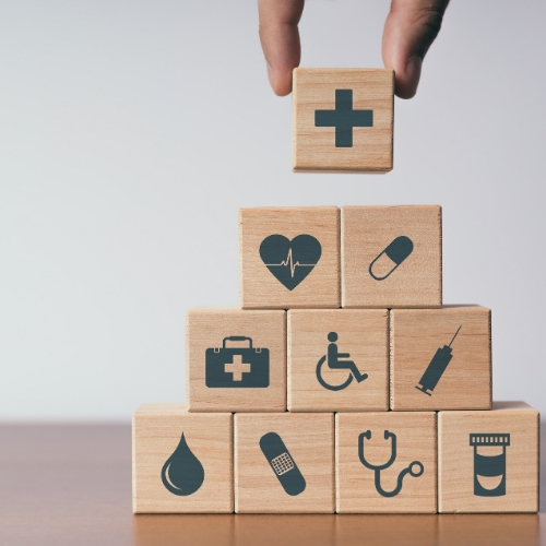 Stacked wooden blocks with medical symbols on them like a heart, pill, stethascope and blood drop